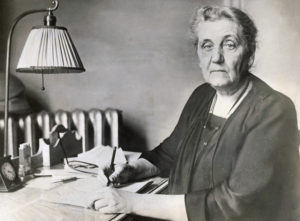 Jane Addams, internationally known social worker and author, writes at her desk. Miss Addams established the social settlement, Hull House, in Chicago in 1889 and founded the American Civil Liberties Union. --- Image by © Bettmann/CORBIS